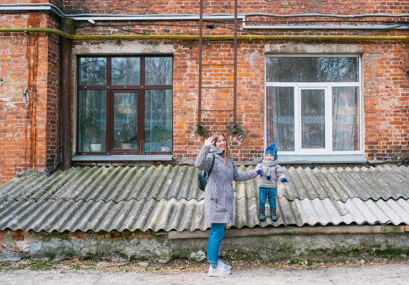 Matka i mała uśmiechnięta syn poza dla rodzinnej fotografii przed czerwonej cegły domem zdjęcia royalty free