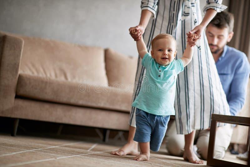 Matka i ojciec w domu uczymy się chodzić ich uśmiechniętej dziecko chłopiec fotografia stock