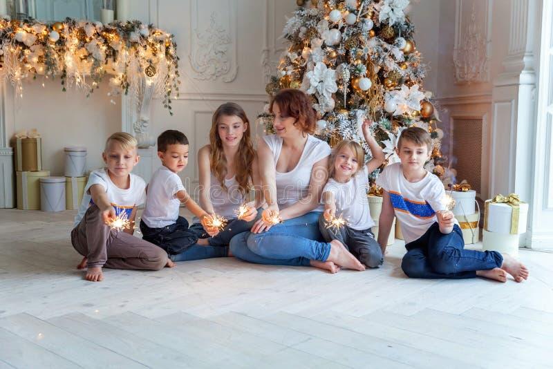 Matka i pięć dzieci bawić się sparkler blisko choinki w domu zdjęcie royalty free