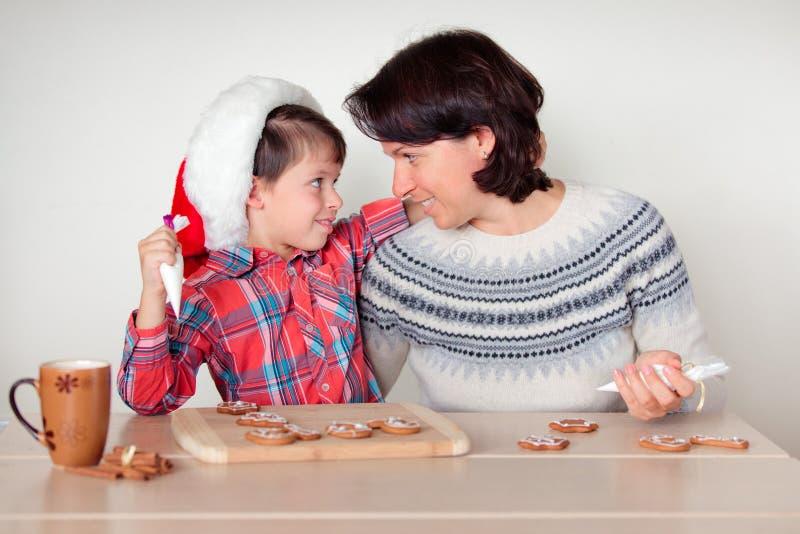Matka i syn dekoruje piernikowych ciastka zdjęcia royalty free