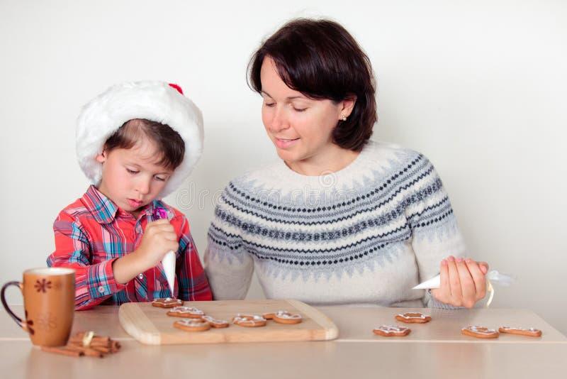 Matka i syn dekoruje piernikowych ciastka zdjęcie stock