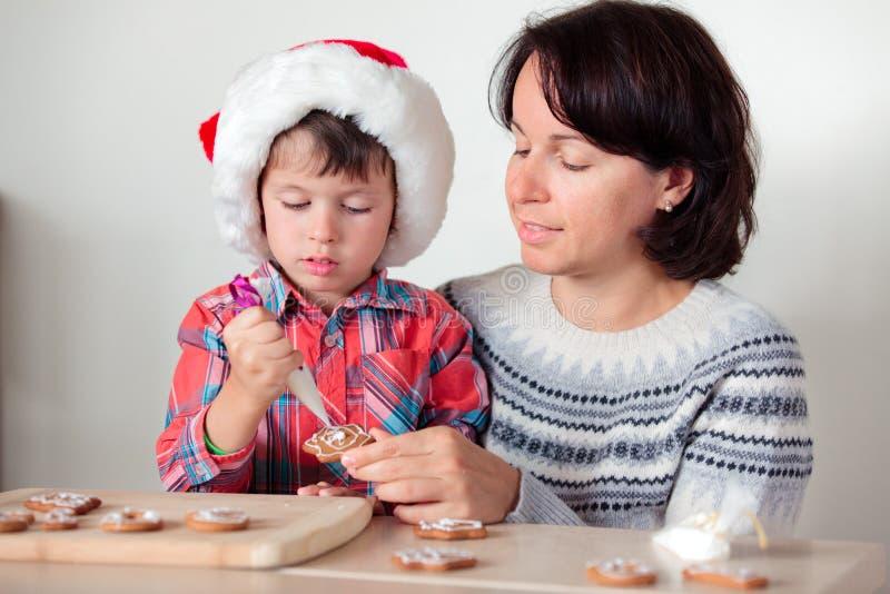 Matka i syn dekoruje piernikowych ciastka obraz royalty free