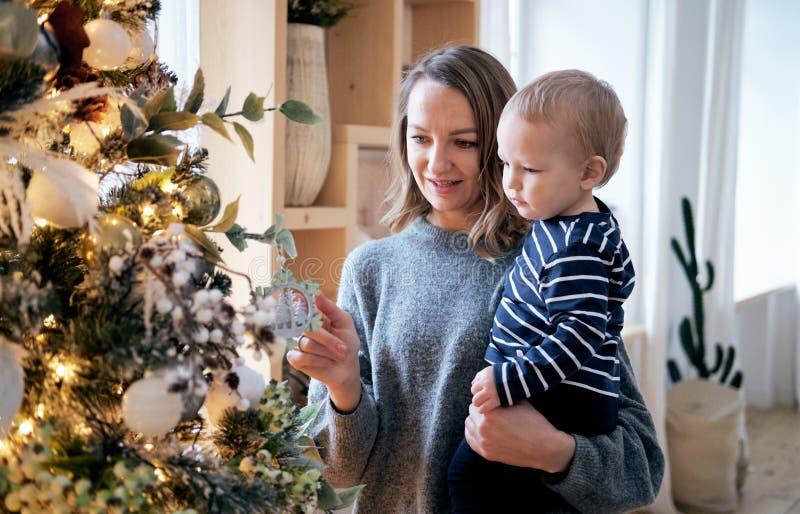 Matka i syn jest ubranym piżamy dekoruje choinki fotografia stock