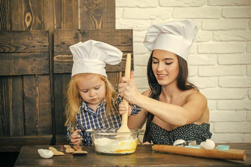 Matka i syn miesza mąkę i jajka w pucharze zdjęcia stock