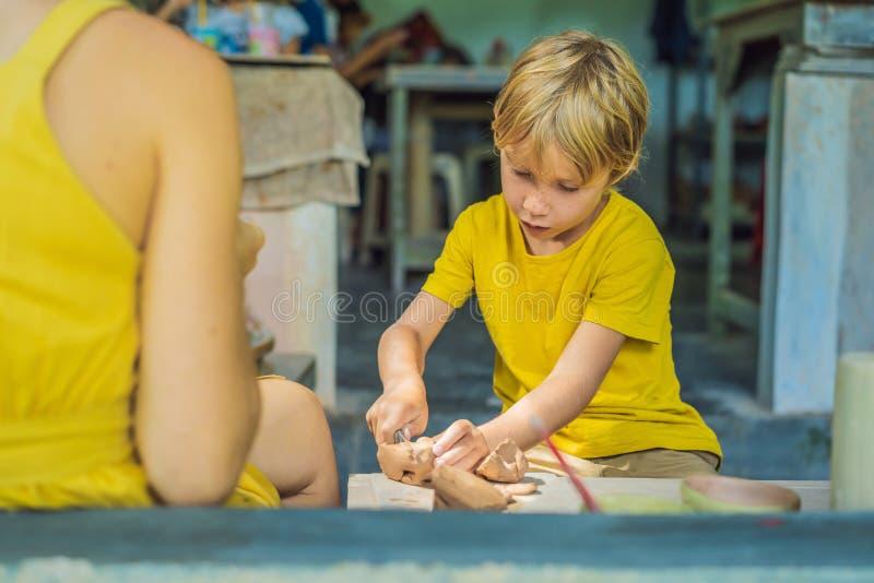 Matka i syn robi ceramicznemu garnkowi w ceramicznym warsztacie Co robić z dziećmi Dziecka życzliwy miejsce fotografia royalty free