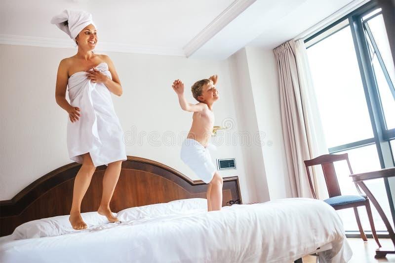 Matka i syn skaczemy na łóżku w luksusowego hotelu pokoju fotografia stock