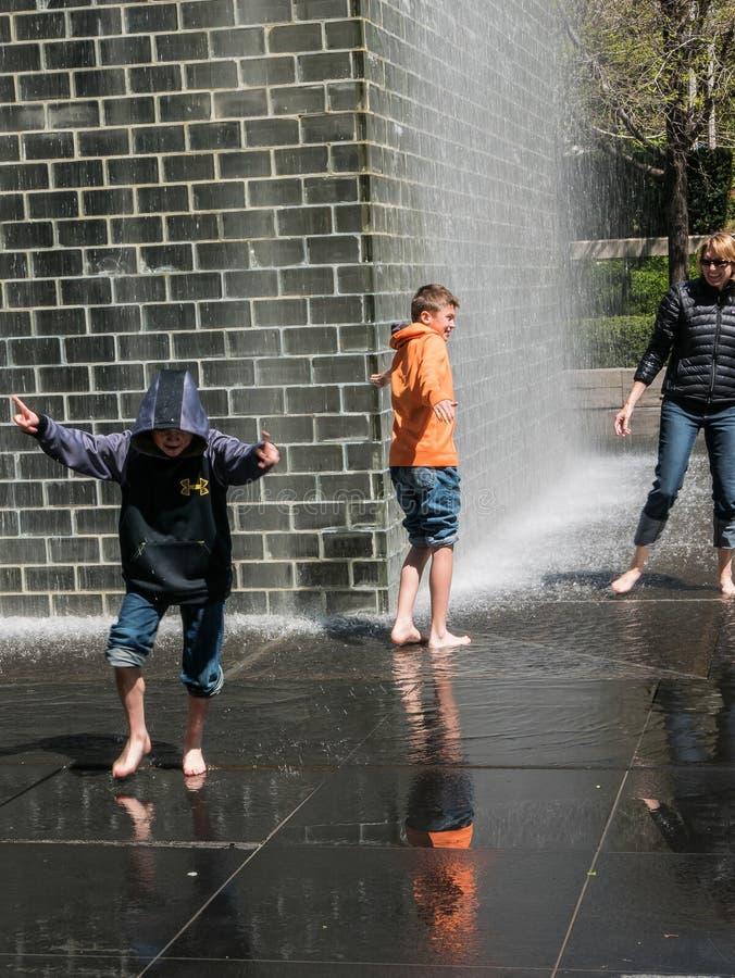 Matka i synowie bawić się w korony fontannie, milenium park, Chicago fotografia royalty free