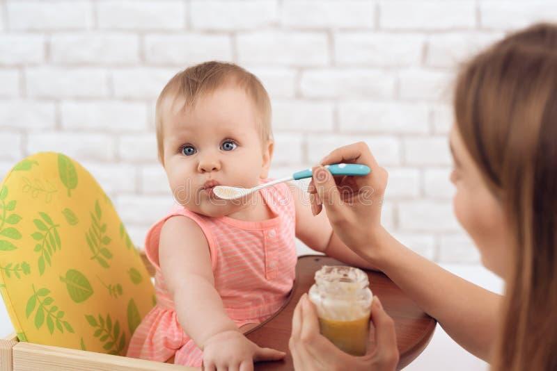 Matka karmi małego dziecka z puree i łyżką zdjęcia royalty free