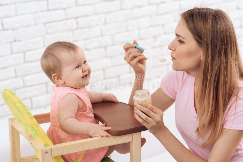 Matka karmi małego uśmiechniętego dziecka z puree obraz royalty free