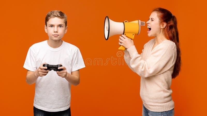 Matka krzyczy przez megafonu przy chłopiec z joystickiem fotografia royalty free