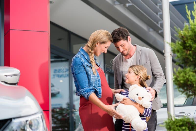 Matka, ojciec i dziecka kupienia samochód przy przedstawicielstwem handlowym, zdjęcia royalty free