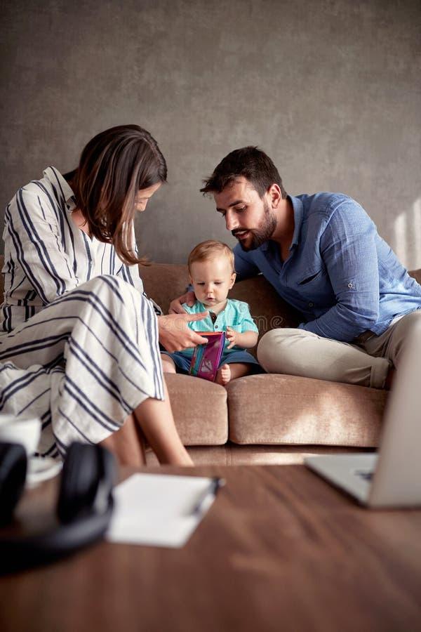 Matka, ojciec i syn, ślicznej chłopiec czytelnicza książka, szczęśliwy życie rodzinne obraz royalty free