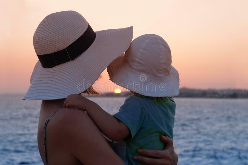 Matka patrzy przez morze na zachód słońca, przytulając dziecko obrazy royalty free