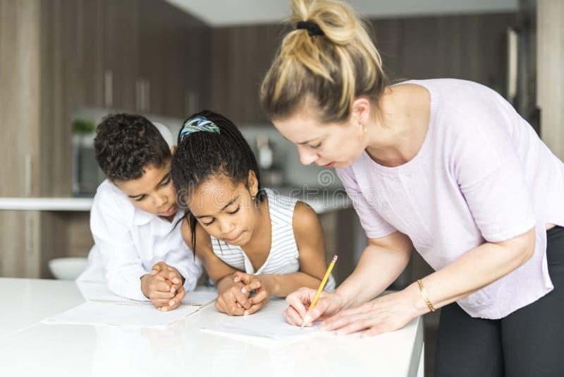 Matka pisze notatce na kuchennym tabl z childs zdjęcie stock
