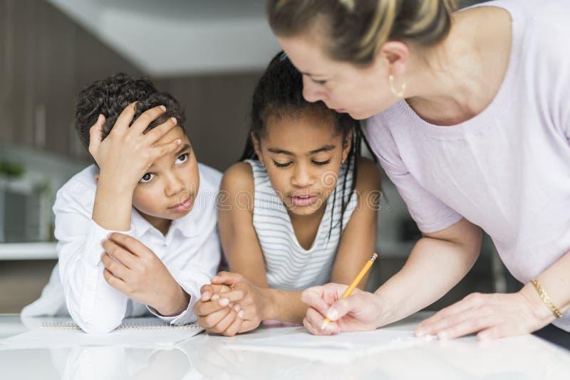 Matka pisze notatce na kuchennym tabl z childs zdjęcia stock