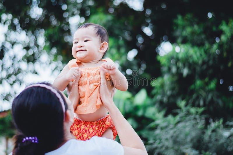 Matka podnosił jej szczęśliwego małego dziecka w ręce nad jej głowa zdjęcia royalty free