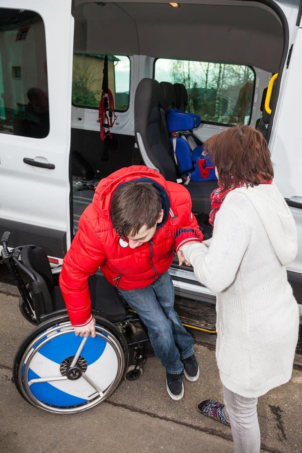 Matka pomaga jej niepełnosprawnego syna z autobusu szkolnego obraz royalty free