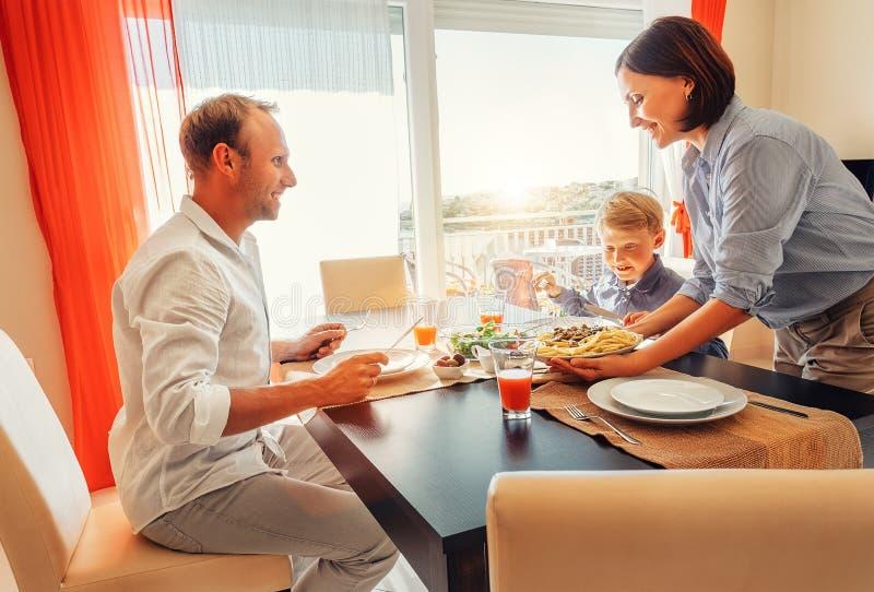 Matka przynosi naczynie posiłek przy stołem jej głodna rodzina zdjęcia royalty free