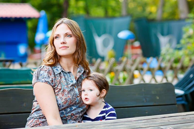 Matka relaksuje wraz z jej małym dzieckiem, urocza berbeć dziewczyna fotografia royalty free