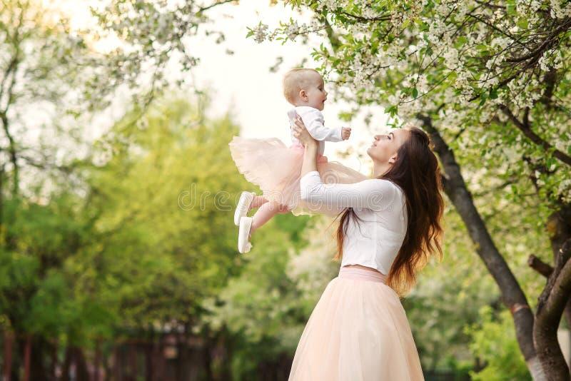 Matka trzyma jej małej córki w jej rękach wśród kwitnących drzew Mama i jej mały dziecko weared różowej rodziny spojrzenia suknię zdjęcie stock