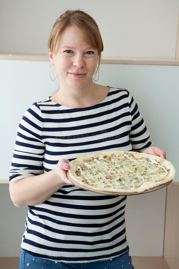 Matka w żeglarza ` s paskującej koszula przynosi dużego pizzy i mienia talerza w rękach, portret zdjęcie stock