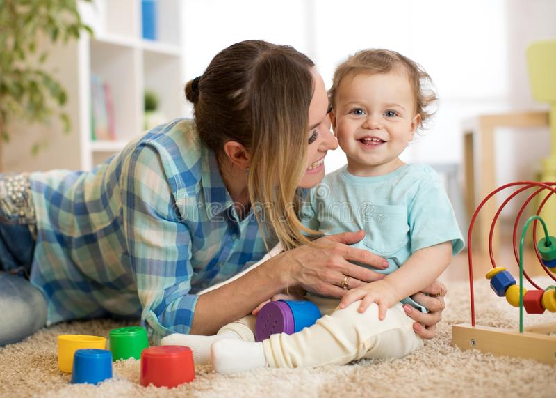 Matka w żywym pokoju bawić się z uśmiechniętym dzieckiem fotografia stock