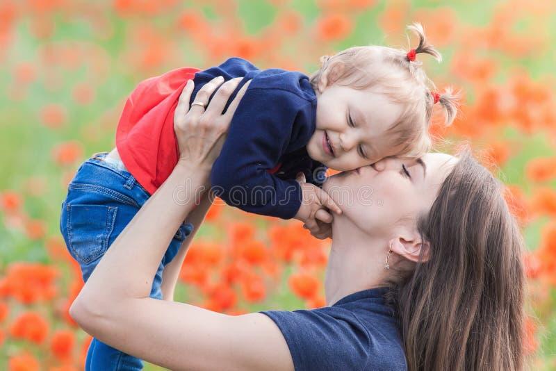 Matka z śmiesznym dzieckiem plenerowym przy makowym kwiatu polem zdjęcia stock