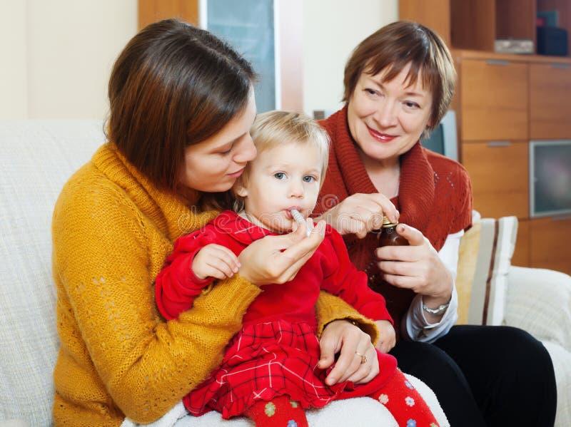 Matka z babcią daje medicament chory dziecko zdjęcia royalty free