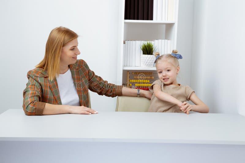 Matka z córką opowiada do siebie siedzieć na biurku obraz royalty free