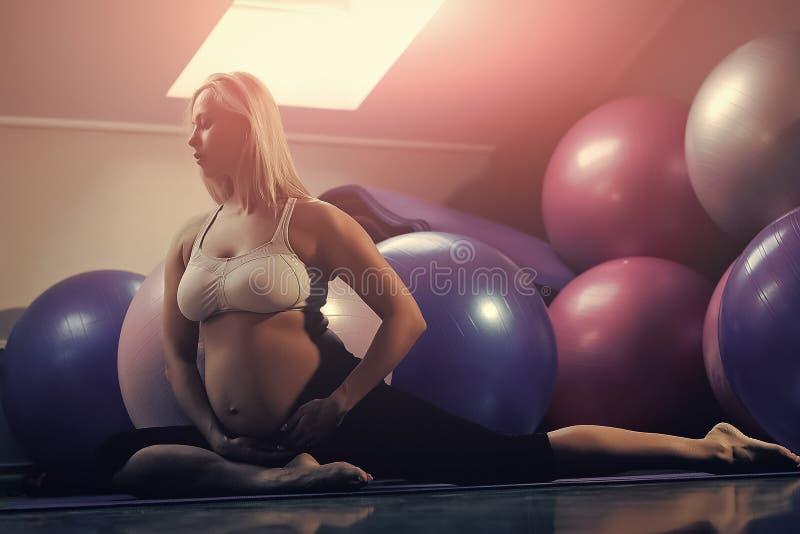 Matka z dużym brzuchem w gym z dysponowanymi piłkami zdjęcia stock