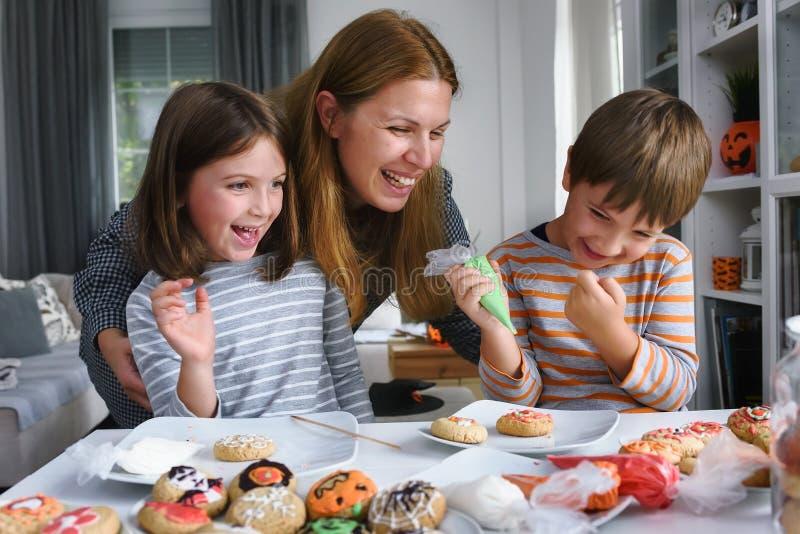 Matka z dzieciakami dekoruje ciastka dla Halloween zdjęcia royalty free