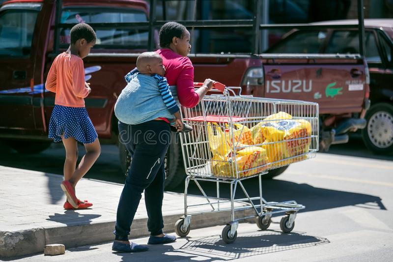 Matka z dzieckiem na jej z powrotem pcha wózek na zakupy w Soweto obraz royalty free
