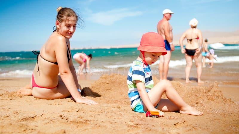 Matka z dziecko chłopiec obsiadaniem na piaskowatej plaży i bawić się z zabawkarskimi samochodami Rodzinny relaksować zabawę na l fotografia royalty free