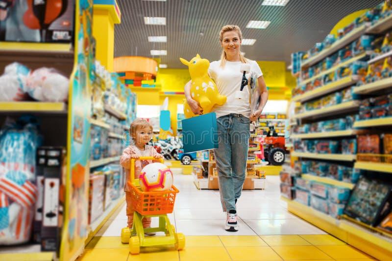 Matka z dziewczyn? kupuje mn?stwo zabawki w sklepie fotografia royalty free