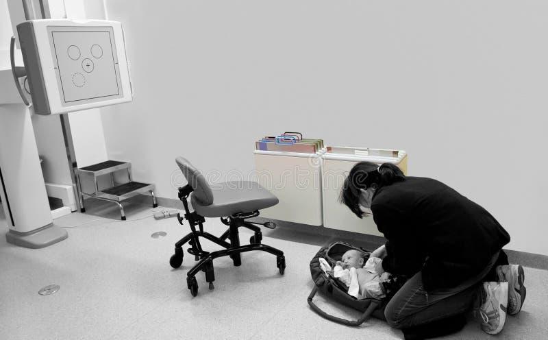 Matka z jej chorą dziecięcą chłopiec wokoło robić Radiologicznemu egzaminowi zdjęcia stock