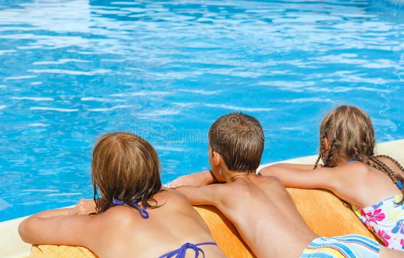 Matka z jej dziećmi blisko pływackiego basenu. obraz royalty free