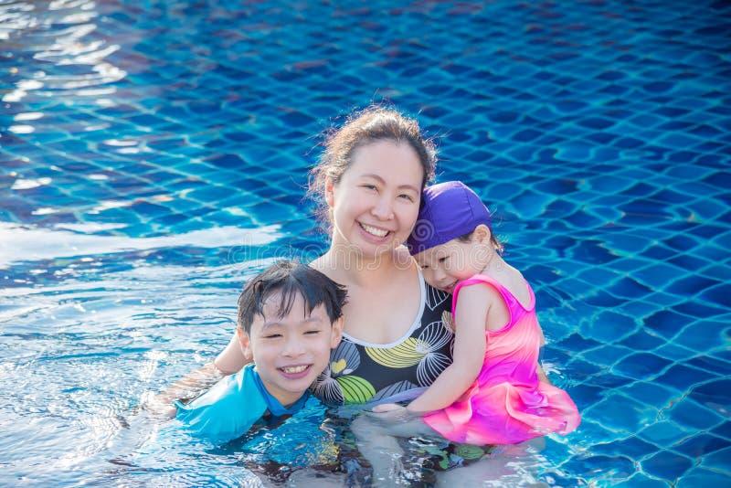 Matka z jej dziećmi w pływackim basenie fotografia stock