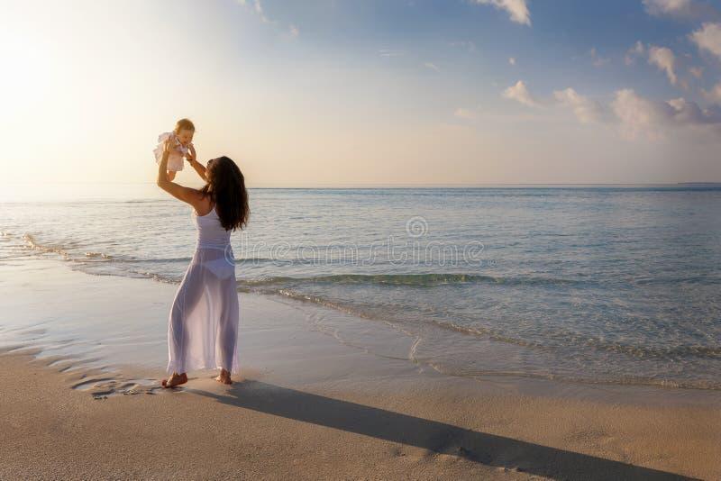 Matka z jej dziewczynką na plaży podczas zmierzchu czasu obraz stock