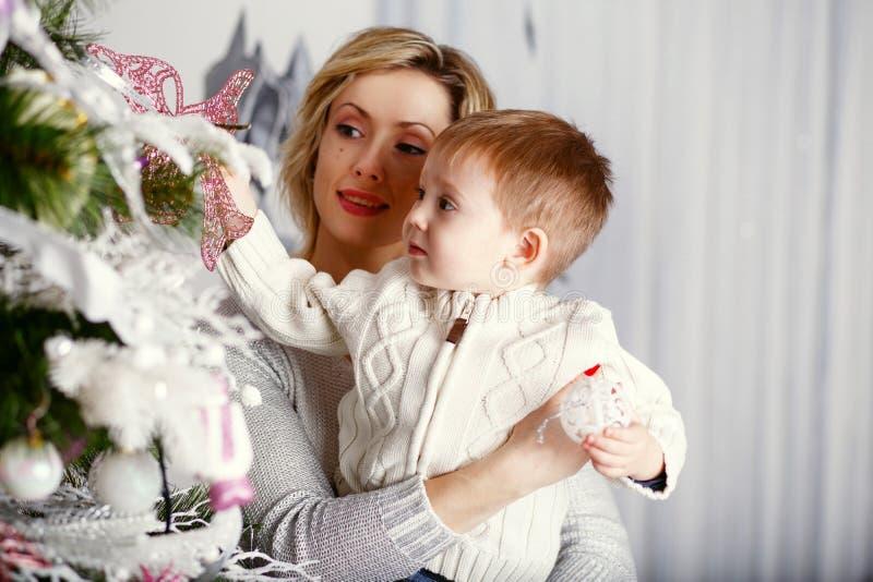 Matka z jej Małym synem dekoruje choinki zdjęcie stock