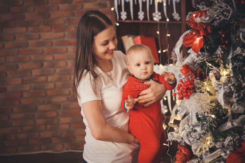 Matka z jej Małym synem dekoruje choinki z zabawkami a obrazy royalty free