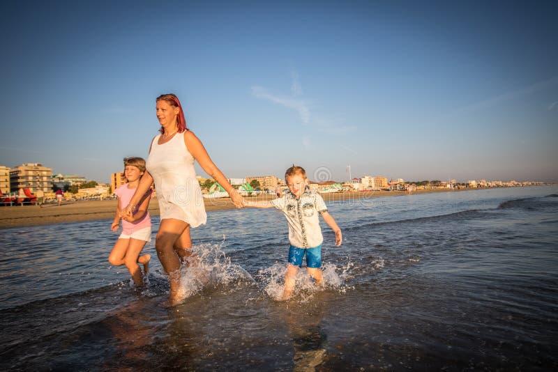 Matka z jej synami bawić się na brzeg obraz stock