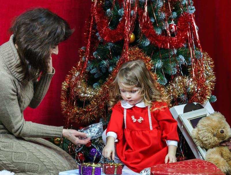 Matka z małymi córki znalezienia bożych narodzeń prezentami obraz royalty free