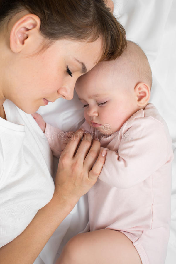 Matka z nowonarodzonym dziecka dosypianiem na łóżku w domu Odgórny widok, zamyka up zdjęcia royalty free