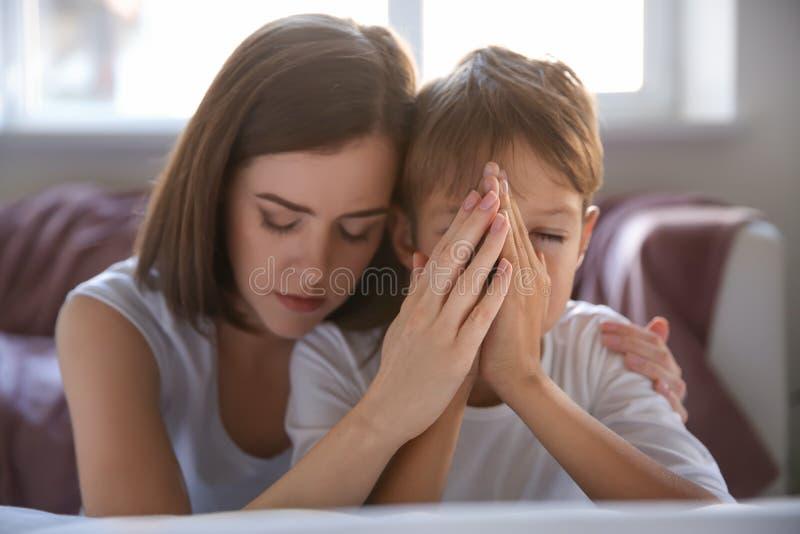 Matka z synem ono modli się blisko łóżka w domu fotografia royalty free
