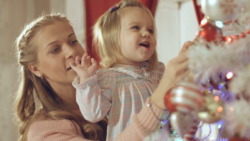 Matka z uroczym dzieckiem dekoruje choinki w domu fotografia stock