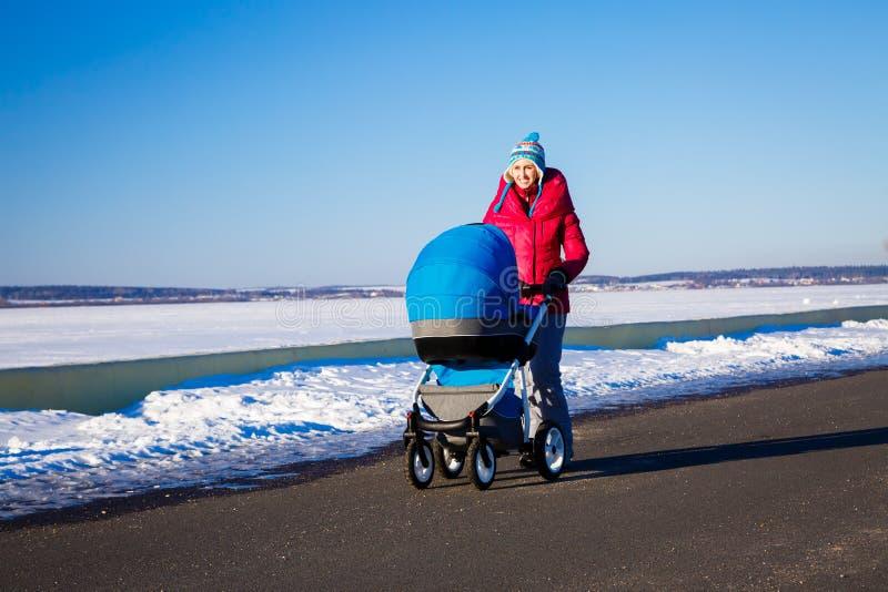 Matka z wózka spacerowego odprowadzeniem w zima parku zdjęcie royalty free