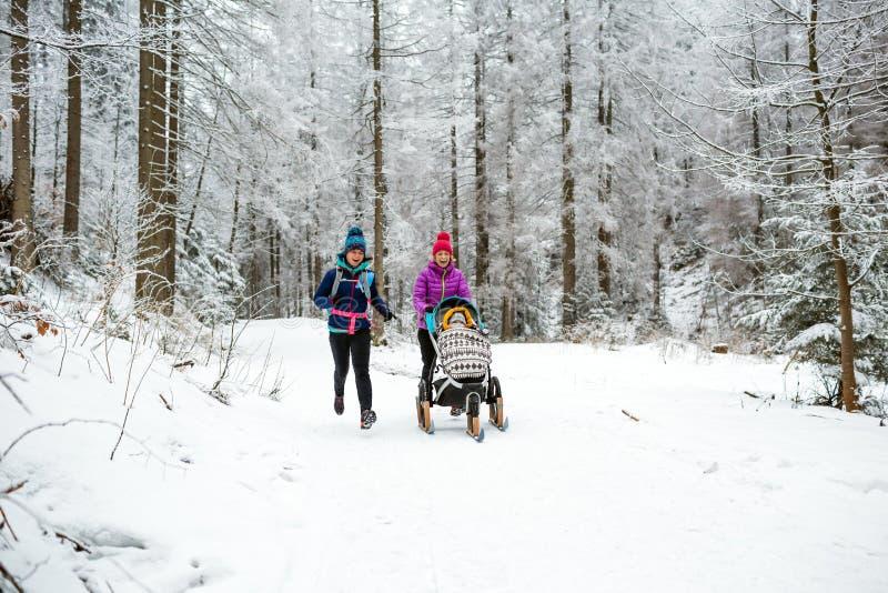Matka z wózkiem spacerowym cieszy się zimę w lesie, rodzinny czas zdjęcie stock