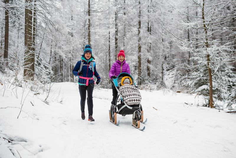 Matka z wózkiem spacerowym cieszy się zimę w lesie, rodzinny czas fotografia royalty free