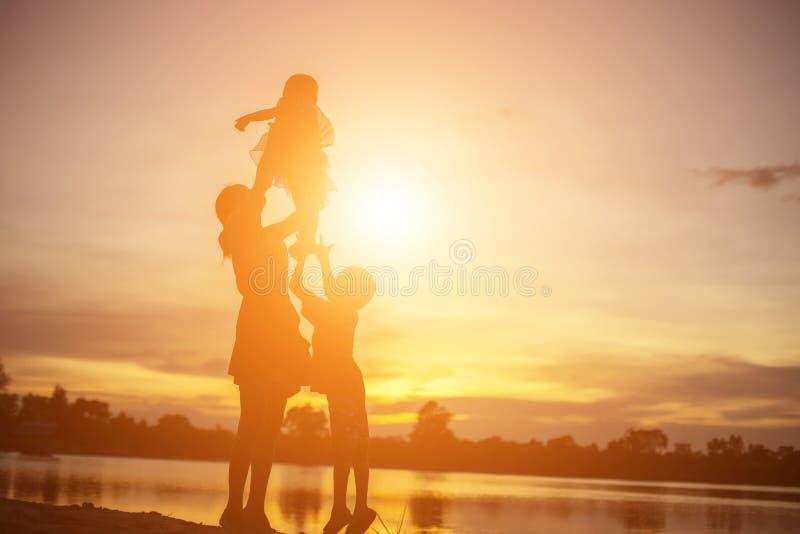 Matka zachęciła syna do pracy na zewnątrz o zachodzie słońca, koncepcja sylwetki fotografia royalty free
