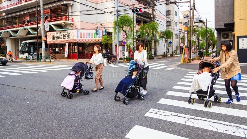 Matki bierze jej dziecka na dziecko tramwaju skrzyżowaniu na ulicie Tokio Asakusa okręg Asakusa jest jeden popularny dla t obrazy royalty free
